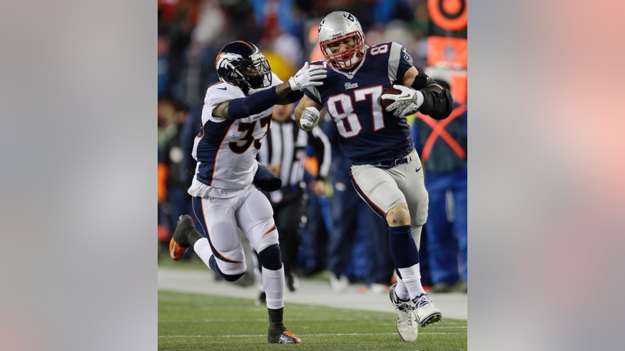 New England Patriots tight end Rob Gronkowski (87) runs from Denver Broncos safety Duke Ihenacho (33) after a catch in the third quarter of an NFL football game Sunday, Nov. 24, 2013, in Foxborough, Mass. (AP Photo/Steven Senne)