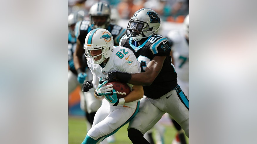 Miami Dolphins wide receiver Brian Hartline (82) is tackled by  Carolina Panthers cornerback Melvin White (23) during the first half of an NFL football game, Sunday, Nov. 24, 2013, in Miami Gardens, Fla. (AP Photo/Lynne Sladky)