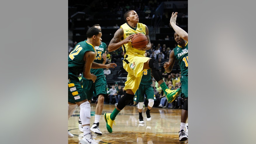 Oregon's Joseph Young, center, drives to the basket through San Francisco's Avry Holmes, left, Mark Tollefsen and Kruize Pinkins, right, during the first half of an NCAA college basketball game in Eugene, Ore.,  on Sunday, Nov. 24, 2013. (AP Photo/Chris Pietsch)