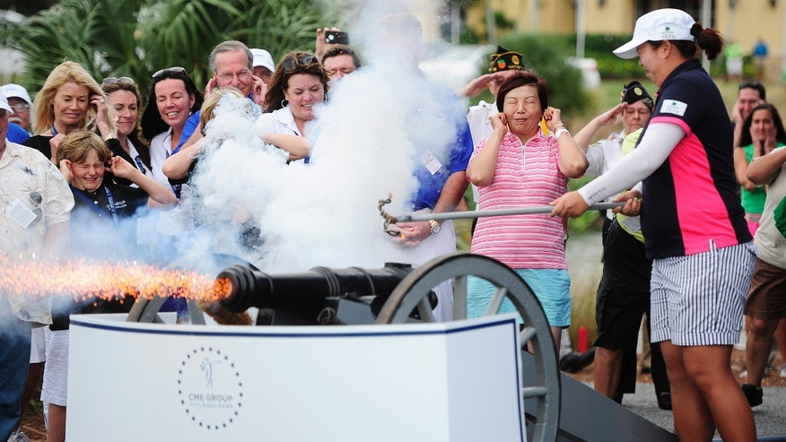 Shanshan Feng, right, starts a new tradition of firing off a cannon as the winner of the CME Group Titleholders LPGA golf tournament Sunday, Nov. 24, 2013 at Tiburon Golf Club in Naples, Fla. Plugging her ears, center is her mother, Yuyan. China's Feng took home the top prize of $700,000 shooting 15-under par for the tournament.  (AP Photo/Naples Daily News, Corey Perrine) FORT MYERS OUT