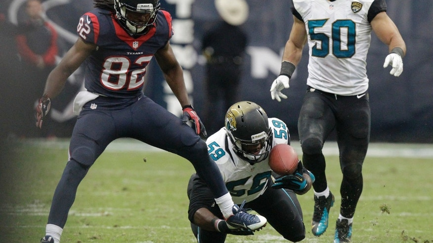 Jacksonville Jaguars defensive end Ryan Davis (59) makes an interception against Houston Texans running back Dennis Johnson (28) during the fourth quarter of an NFL football game Sunday, Nov. 24, 2013, in Houston. At right is the Jaguars outside linebacker Russell Allen (50). The Jaguars won 13-6. (AP Photo/Patric Schneider)