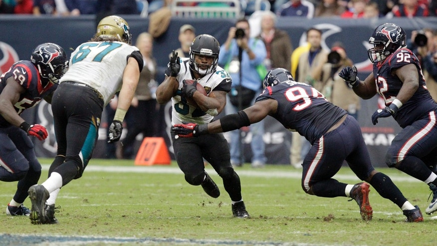 Jacksonville Jaguars running back Maurice Jones-Drew (32) tries to maneuver around Houston Texans defensive end Antonio Smith (94) during the fourth quarter of an NFL football game Sunday, Nov. 24, 2013, in Houston. (AP Photo/Patric Schneider)