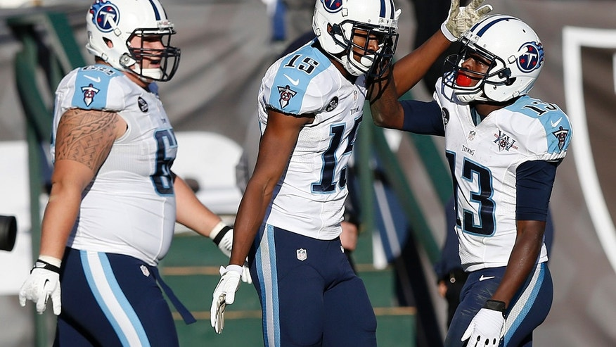 Tennessee Titans wide receiver Justin Hunter (15) celebrates with wide receiver Kendall Wright (13) and center Brian Schwenke, left, after Hunter scored on a 54-yard touchdown reception during the third quarter of an NFL football game in Oakland, Calif., Sunday, Nov. 24, 2013. (AP Photo/Beck Diefenbach)
