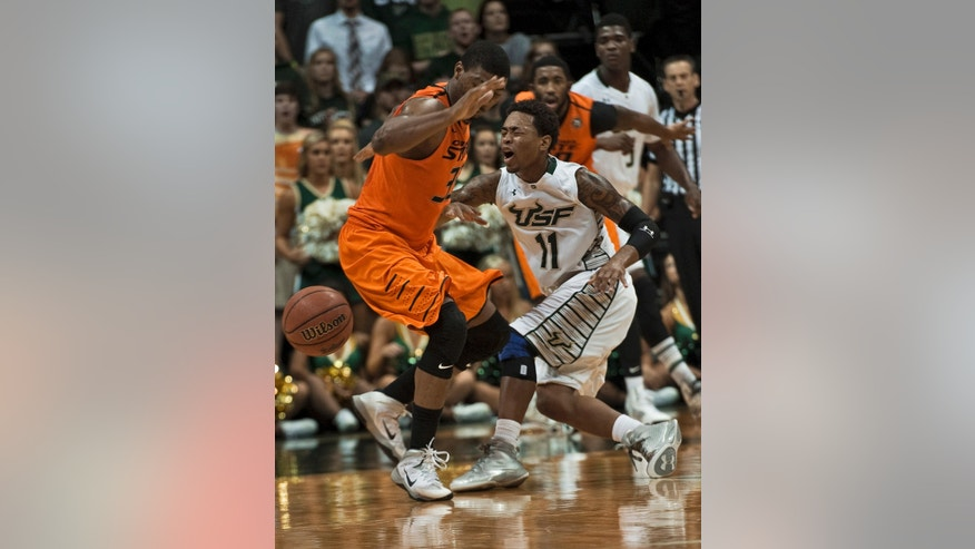 South Florida's Anthony Collins (11) loses the ball as he collides with Oklahoma State's Marcus Smart, left, during the first half of an NCAA college basketball game Monday, Nov. 25, 2013, in Tampa, Fla. (AP Photo/Steve Nesius)