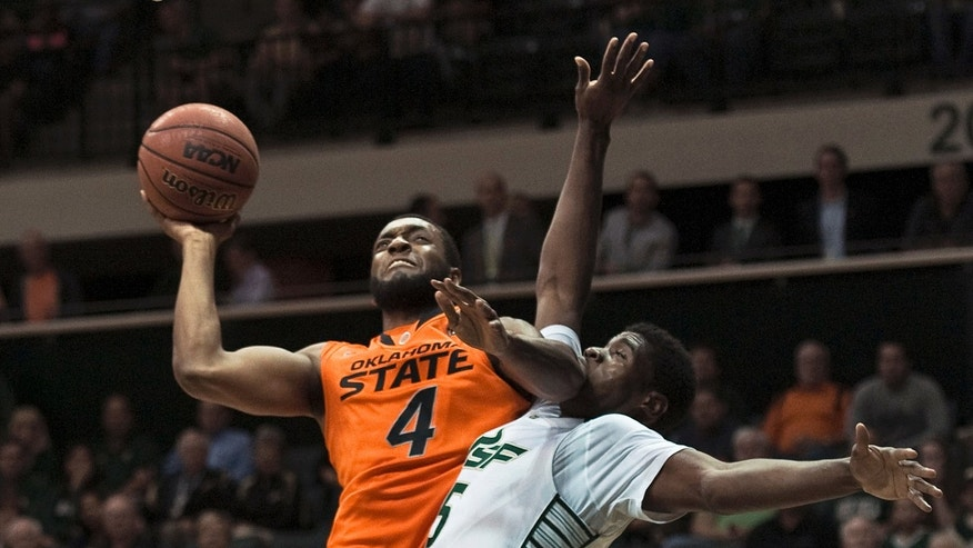 Oklahoma State's Brian Williams (4) goes up for a shot under pressure from South Florida's John Egbunu, right, during the first half of an NCAA college basketball game Monday, Nov. 25, 2013, in Tampa, Fla. (AP Photo/Steve Nesius)