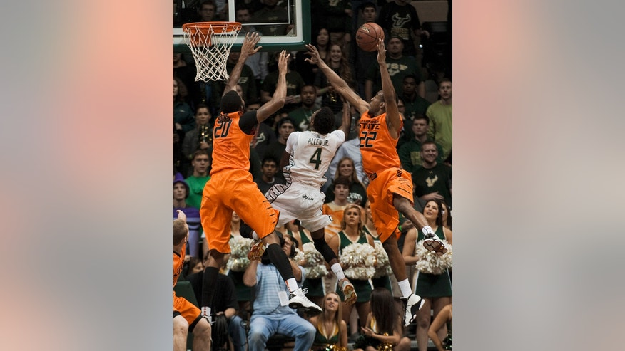 Oklahoma State's Michael Cobbins (20) and Markel Brown (22) leap for a rebound with South Florida's Corey Allen  Jr.  during the first half of an NCAA college basketball game Monday, Nov. 25, 2013, in Tampa, Fla. (AP Photo/Steve Nesius)