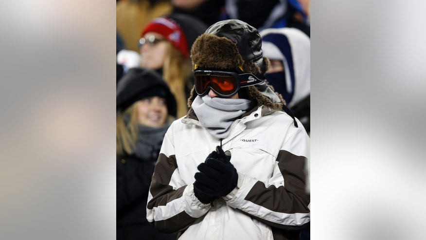 A fan is bundled against the cold in the second quarter of an NFL football game between the New England Patriots and the Denver Broncos Sunday, Nov. 24, 2013, in Foxborough, Mass. (AP Photo/Elise Amendola)