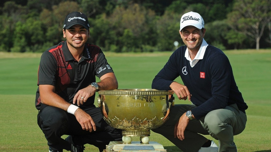 Jason Day, left, of Australia and compatriot Adam Scott pose with the World Cup of Golf trophy for photographers after winning the team event at Royal Melbourne Golf Course in Australia, Sunday, Nov. 24, 2013. (AP Photo/Andy Brownbill)