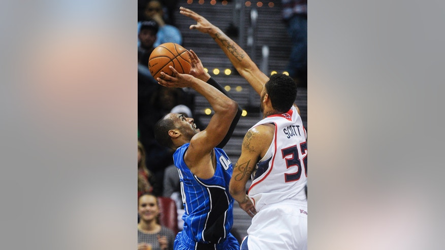 Orlando Magic guard Arron Afflalo tries to get off a shot before Atlanta Hawks power forward Mike Scott (32) blocks it during the first half of an NBA basketball game on Tuesday, Nov. 26, 2013, in Atlanta. (AP Photo/John Amis)
