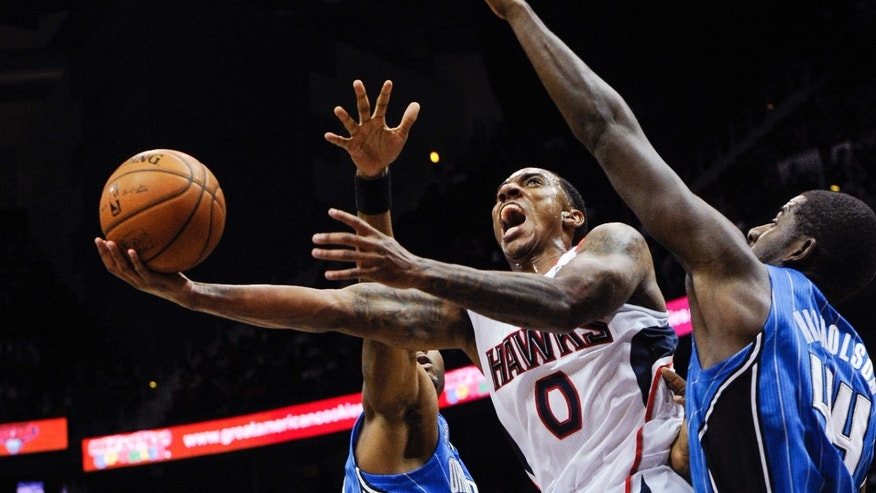 Atlanta Hawks point guard Jeff Teague, (0) goes to the basket between the defense of Orlando Magic point guard E'Twaun Moore, left, and forward Andrew Nicholson, of Canada, during the first half of an NBA basketball game on Tuesday, Nov. 26, 2013, in Atlanta. (AP Photo/John Amis)