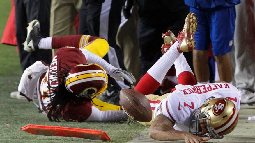 Washington Redskins strong safety Brandon Meriweather collides with San Francisco 49ers quarterback Colin Kaepernick as they slide out-of-bounds during the second half of an NFL football game in Landover, Md., Monday, Nov. 25, 2013. The 49ers defeated the Redskins 27-6. (AP Photo/Mark Tenally)
