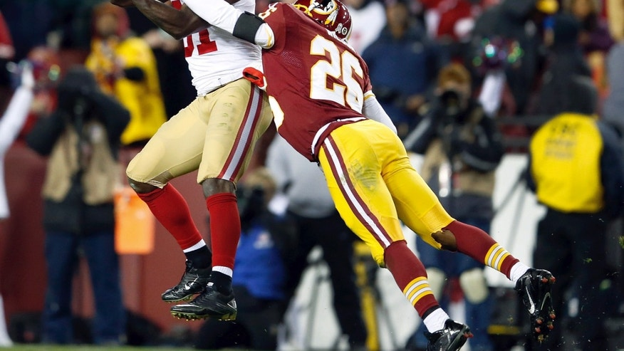San Francisco 49ers wide receiver Anquan Boldin pulls in a pass under pressure from Washington Redskins cornerback Josh Wilson during the second half of an NFL football game in Landover, Md., Monday, Nov. 25, 2013. (AP Photo/Evan Vucci)
