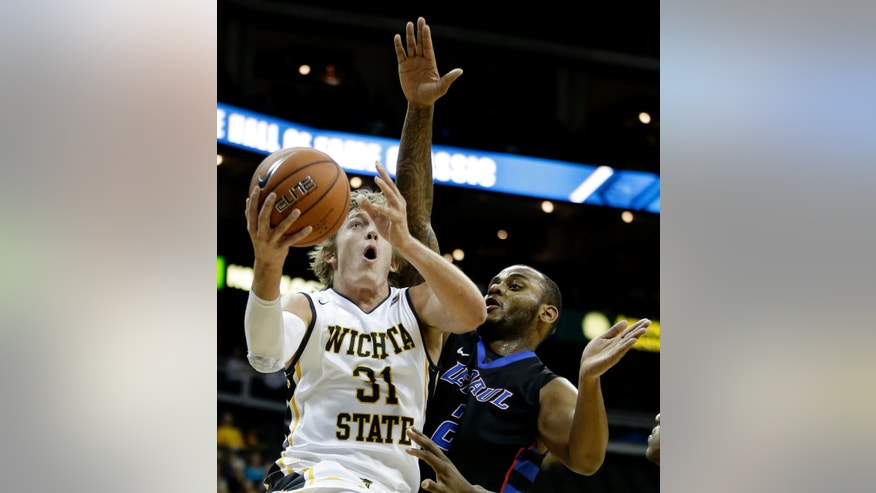 Wichita State's Ron Baker (31) gets past DePaul's Tommy Hamilton IV (2) to put up a shot during the first half of an NCAA college basketball game Monday, Nov. 25, 2013, in Kansas City, Mo. (AP Photo/Charlie Riedel)