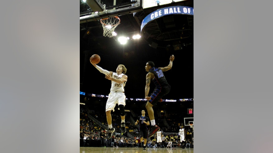 Wichita State's Ron Baker (31) gets past DePaul's Brandon Young (20) to put up a shot during the first half of an NCAA college basketball game Monday, Nov. 25, 2013, in Kansas City, Mo. (AP Photo/Charlie Riedel)