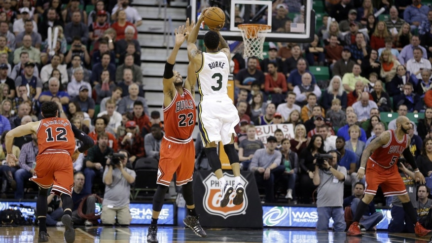 Utah Jazz's Trey Burke (3) shoots as Chicago Bulls' Taj Gibson (22) defends in overtime during an NBA basketball game Monday, Nov. 25, 2013, in Salt Lake City. The Jazz won 89-83. (AP Photo/Rick Bowmer)