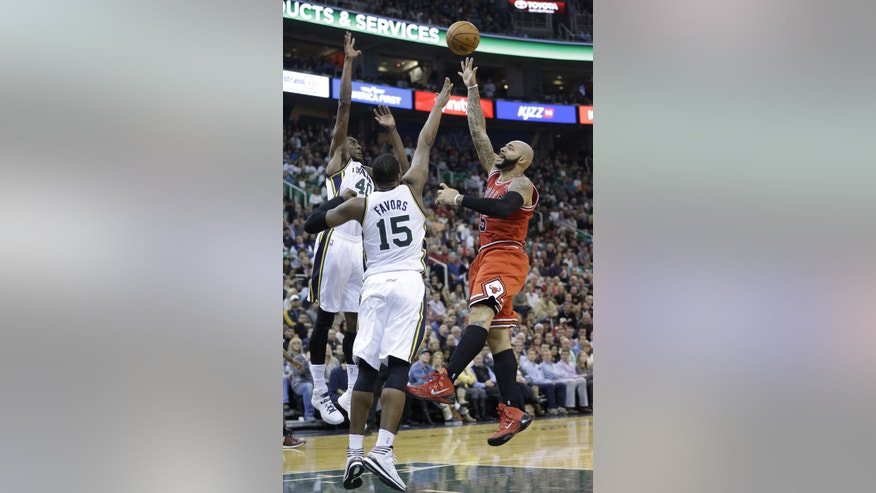 Chicago Bulls' Carlos Boozer, right, shoots as Utah Jazz's Jeremy Evans (40) and teammate Derrick Favors (15) defend in the second quarter during an NBA basketball game Monday, Nov. 25, 2013, in Salt Lake City. (AP Photo/Rick Bowmer)