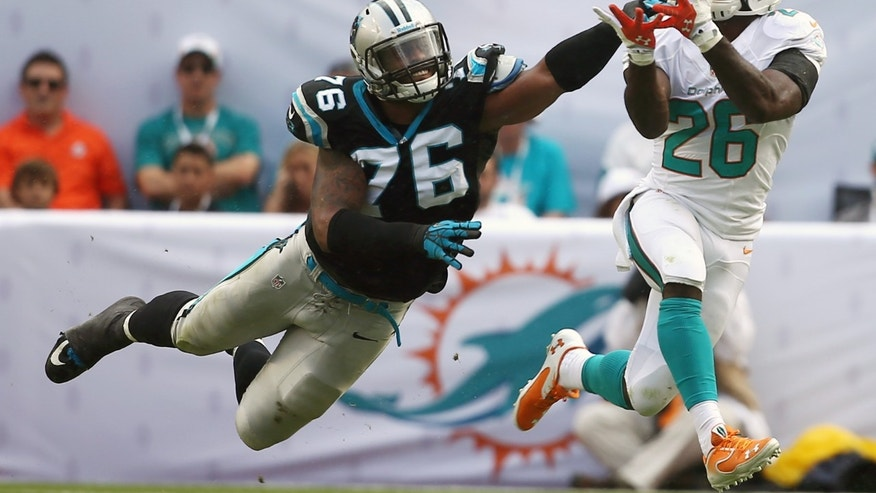 Miami Dolphins running back Lamar Miller (26) grabs a pass as Carolina Panthers defensive end Greg Hardy (76) applies pressure during the first half of an NFL football game on Sunday, Nov. 24, 2013, in Miami Gardens, Fla. (AP Photo/J Pat Carter)