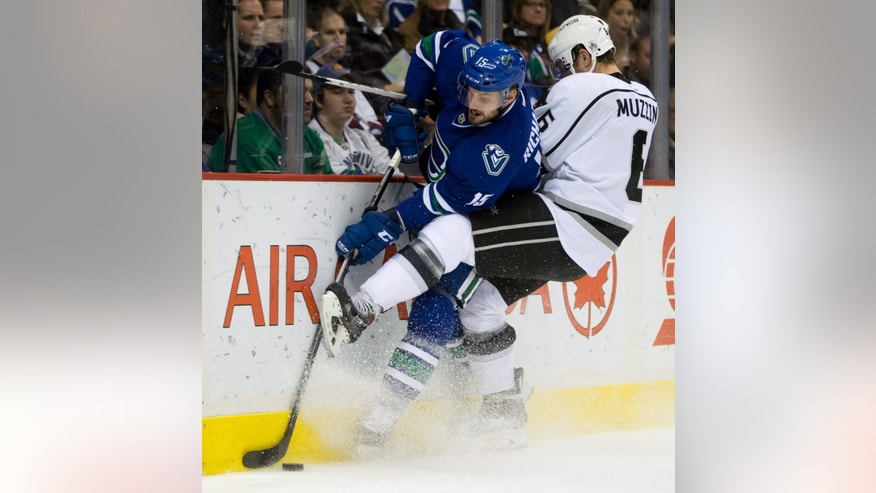Los Angeles Kings' Jake Muzzin, right, checks Vancouver Canucks' Brad Richardson during first period NHL hockey action in Vancouver, British Columbia, on Monday, Nov. 25, 2013. (AP Photo/The Canadian Press, Darryl Dyck)