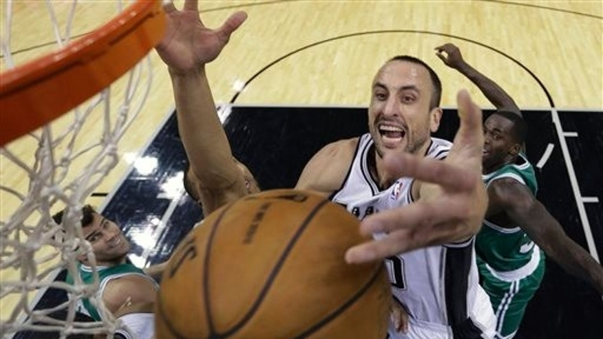 Manu Ginobili of Argentina reaches over Boston Celtics' Courtney Lee on Wednesday,  Nov. 20, 2013, in San Antonio.