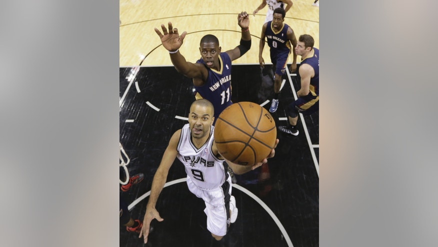 San Antonio Spurs' Tony Parker (9), of France, scores in front of New Orleans Pelicans' Jrue Holiday (11) during the first half of an NBA basketball game, Monday, Nov. 25, 2013, in San Antonio. (AP Photo/Eric Gay)