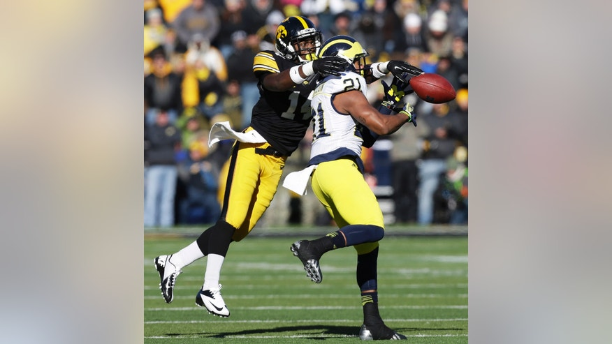 Iowa defensive back Desmond King, left, breaks up a pass intended for Michigan wide receiver Jeremy Gallon during the second half of an NCAA college football game, Saturday, Nov. 23, 2013, in Iowa City, Iowa. Iowa won 24-21. (AP Photo/Charlie Neibergall)