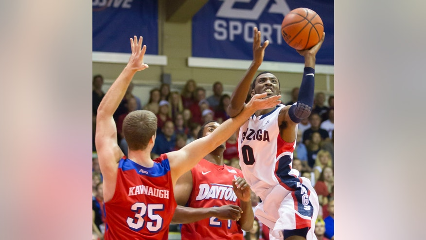 Gonzaga guard Gerard Coleman (0) gets around Dayton's Matt Kavanaugh (35) and Dyshawn Pierre, center, to take a shot in the first half of an NCAA college basketball game at the Maui Invitational on Monday, Nov. 25, 2013, in Lahaina, Hawaii. (AP Photo/Eugene Tanner)
