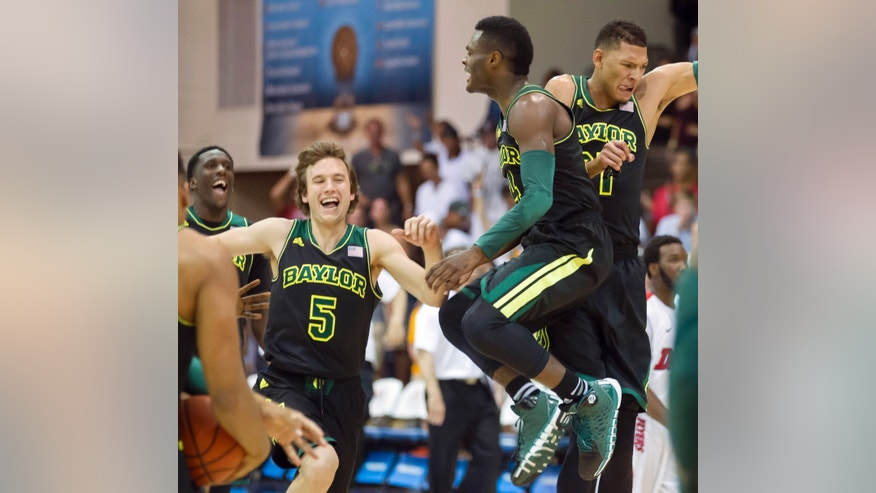 Baylor guard Brady Heslip (5) and his teammates guard Gary Franklin, center, and center Isaiah Austin, right,  celebrat their 67-66 win over Dayton in an NCAA college basketball game at the Maui Invitational on Tuesday, Nov. 26, 2013, in Lahaina, Hawaii.  (AP Photo/Eugene Tanner)