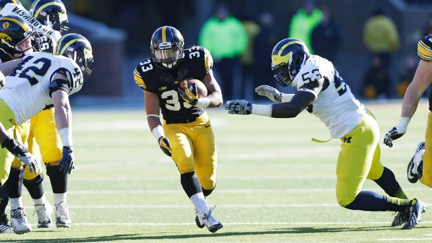 Iowa running back Jordan Canzeri (33) runs from Michigan defenders Ben Gedeon, left, and Mario Ojemudia (53) during the second half of an NCAA college football game, Saturday, Nov. 23, 2013, in Iowa City, Iowa. Iowa won 24-21. (AP Photo/Charlie Neibergall)