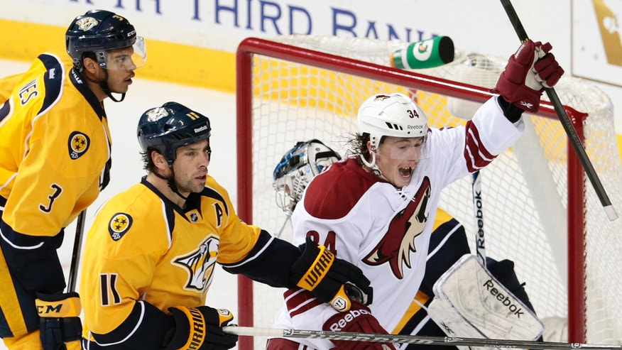 Phoenix Coyotes forward Tim Kennedy (34) celebrates after scoring a goal against the Nashville Predators in the second period of an NHL hockey game Monday, Nov. 25, 2013, in Nashville, Tenn. Watching are the Predators   Seth Jones (3) and David Legwand (11). (AP Photo/Mark Humphrey)