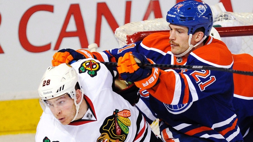 Edmonton Oilers' Andrew Ference (21) defends Chicago Blackhawks' Ben Smith (28) during the second period of an NHL hockey game in Edmonton, Alberta, on Monday, Nov. 25, 2013. (AP Photo/The Canadian Press, John Ulan)