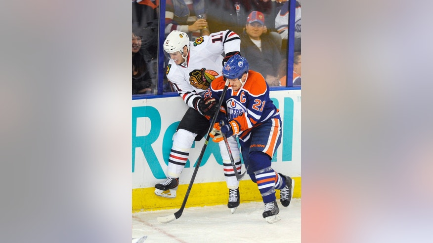 Edmonton Oilers' Andrew Ference (21) checks Chicago Blackhawks Jeremy Morin (11) during the second period of an NHL hockey game in Edmonton, Alberta, on Monday, Nov. 25, 2013. (AP Photo/The Canadian Press, John Ulan)