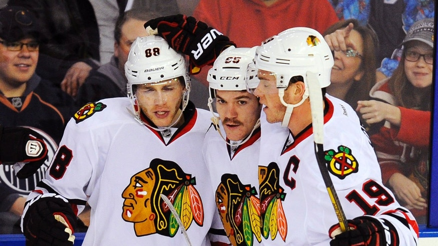 Chicago Blackhawks' Jonathan Toews (19) and Andrew Shaw (65) congratulate Patrick Kane (88) on his goal on the Edmonton Oilers during the first period of an NHL hockey game in Edmonton, Alberta, on Monday, Nov. 25, 2013. (AP Photo/The Canadian Press, John Ulan)