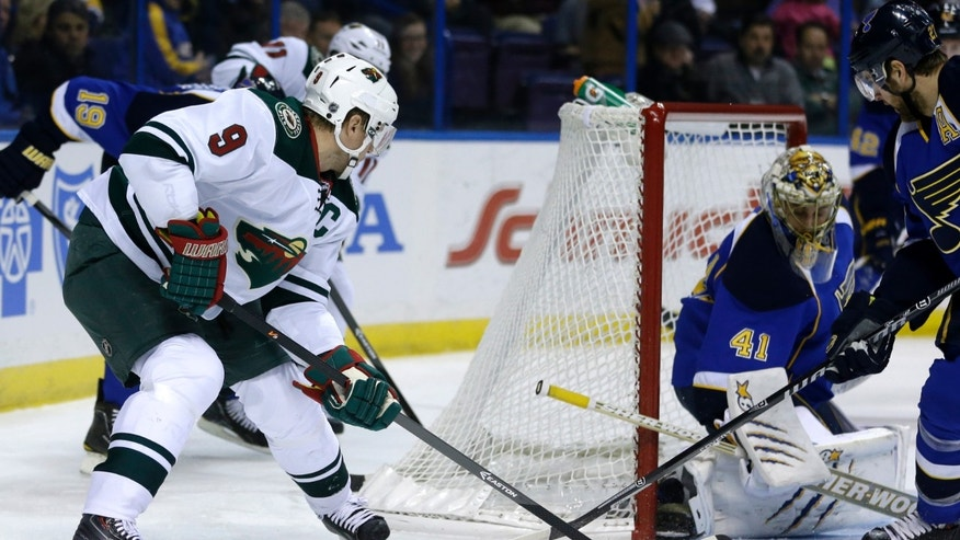 Minnesota Wild's Mikko Koivu (9), of Finland, tries to get off a shot as St. Louis Blues goalie Jaroslav Halak, of Slovakia, defends during the first period of an NHL hockey game Monday, Nov. 25, 2013, in St. Louis. (AP Photo/Jeff Roberson)