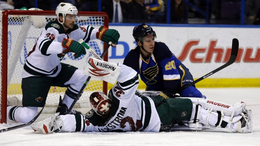 Minnesota Wild goalie Niklas Backstrom, of Finland, falls after colliding with St. Louis Blues' Alexander Steen (20) as Wild's Nate Prosser, left, watches during the second period of an NHL hockey game Monday, Nov. 25, 2013, in St. Louis. (AP Photo/Jeff Roberson)
