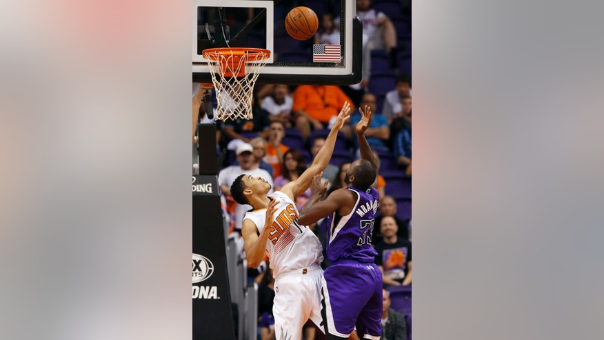 Sacramento Kings' Luc Mbah a Moute, right, of Cameroon, goes up for a shot over Phoenix Suns' Gerald Green, left, during the second half of an NBA basketball game Wednesday, Nov. 20, 2013, in Phoenix. The Kings won 113-106. (AP Photo/Ross D. Franklin)