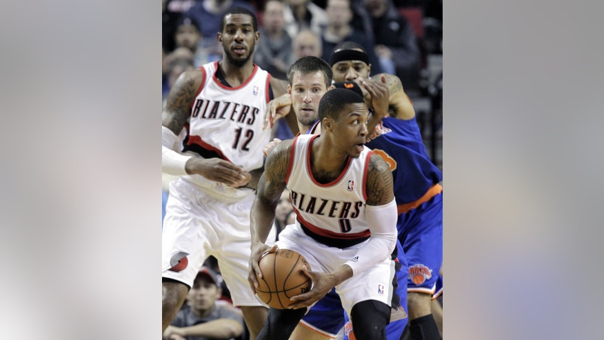 Portland Trail Blazers guard Damian Lillard, right, looks for room to maneuver against New York Knicks guard Beno Udrih, from Slovenia, during the first half of an NBA basketball game in Portland, Ore., Monday, Nov. 25, 2013.  In the background are Trail Blazers forward LaMarcus Aldridge, left, and New York Knicks forward Kenyon Martin. (AP Photo/Don Ryan)