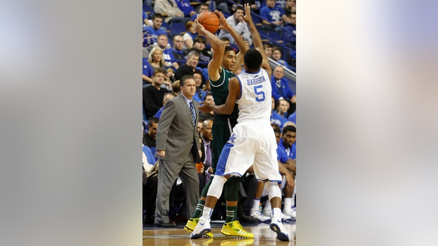 Eastern Michigan's Karrington Ward (14) is pressured by Kentucky's  Andrew Harrison (5) as Kentucky head coach John Calipari, left, looks on during the first half of an NCAA college basketball game, Wednesday, Nov. 27, 2013, in Lexington, Ky. (AP Photo/James Crisp)