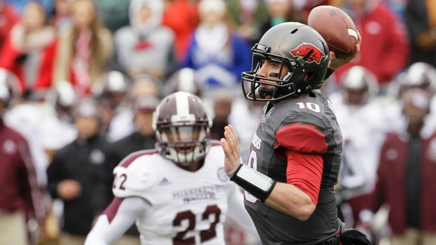 Arkansas quarterback Brandon Allen (10) passes in front of Mississippi State linebacker Matthew Wells (22) in the first half of an NCAA college football game in Little Rock, Ark., Saturday, Nov. 23, 2013. (AP Photo/Danny Johnston)