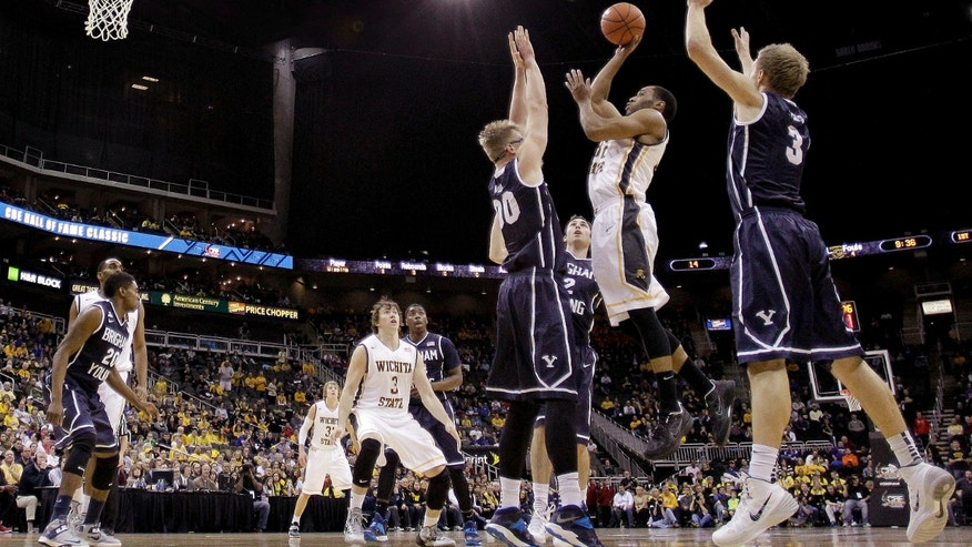 Wichita State's Tekele Cotton gets past Brigham Young's Tyler Haws (3) and Eric Mika (00) to put up a shot during the first half of an NCAA college basketball game Tuesday, Nov. 26, 2013, in Kansas City, Mo. (AP Photo/Charlie Riedel)