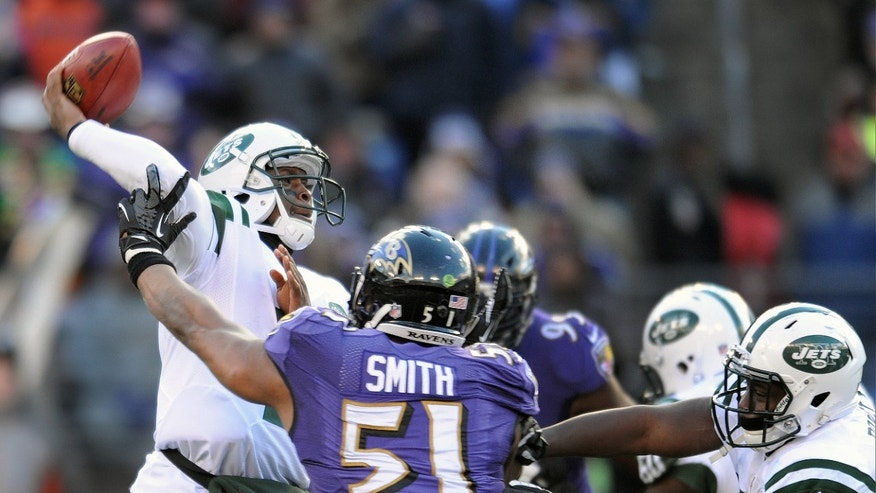 New York Jets quarterback Geno Smith, left, passes the ball under pressure from Baltimore Ravens inside linebacker Daryl Smith (51) during the first half of an NFL football game in Baltimore, Md., Sunday, Nov. 24, 2013. (AP Photo/Gail Burton)