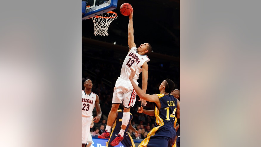 Arizona's Nick Johnson (13) goes to the basket against Drexel's Damion Lee (14) during the first half of an NCAA college basketball game in the semifinals of the NIT Season Tip-off tournament Wednesday, Nov. 27, 2013, in New York. (AP Photo/Jason DeCrow)