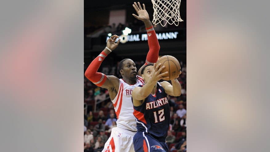 Atlanta Hawks' John Jenkins (12) goes to the basket with Houston Rockets' Dwight Howard, left, at his back in the first half of an NBA basketball game Wednesday, Nov. 27, 2013, in Houston. (AP Photo/Pat Sullivan)