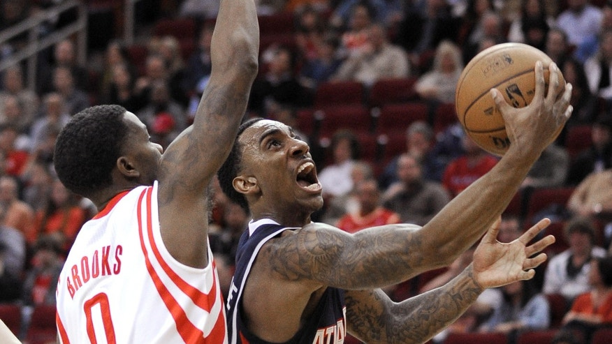 Atlanta Hawks' Jeff Teague, right, goes to the basket guarded by Houston Rockets' Aaron Brooks (0) in the first half of an NBA basketball game Wednesday, Nov. 27, 2013, in Houston. (AP Photo/Pat Sullivan)