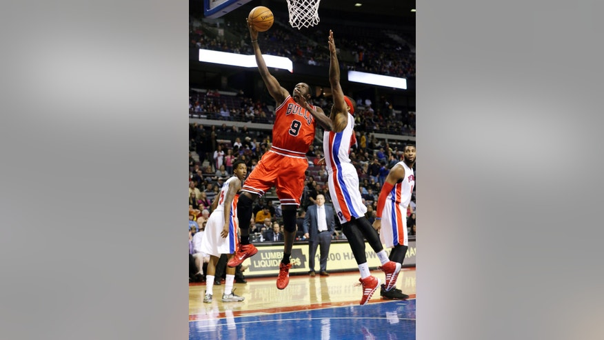 Chicago Bulls forward Luol Deng (9) makes a layup defended by Detroit Pistons forward Josh Smith during the first quarter of an NBA basketball game in Auburn Hills, Mich., Wednesday, Nov. 27, 2013. (AP Photo/Carlos Osorio)