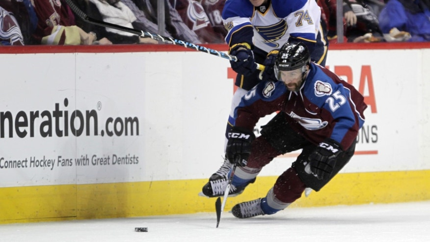 St. Louis Blues right wing T.J. Oshie (74) collides with Colorado Avalanche center Maxime Talbot (25) chasing the puck during the first period of an NHL hockey game in Denver on Wednesday, Nov. 27, 2013. (AP Photo/Joe Mahoney)