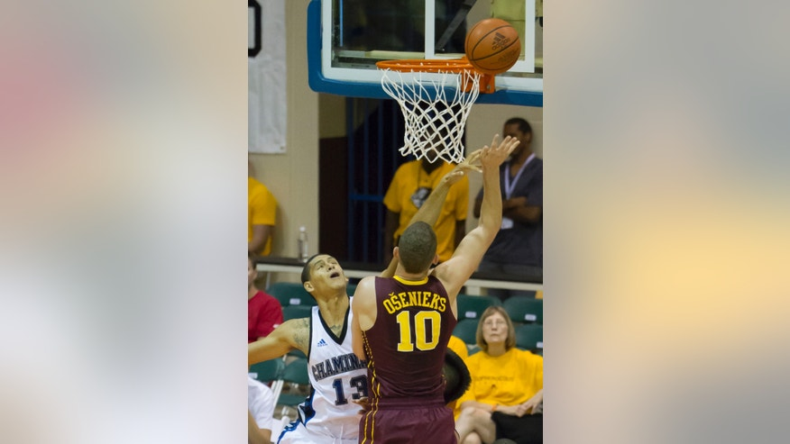 Minnesota forward Oto Osenieks (10) puts up a shot over Chaminade forward Frankie Eteuati (13) in the first half of an NCAA college basketball game at the Maui Invitational on Wednesday, Nov. 27, 2013, in Lahaina, Hawaii.  (AP Photo/Eugene Tanner)