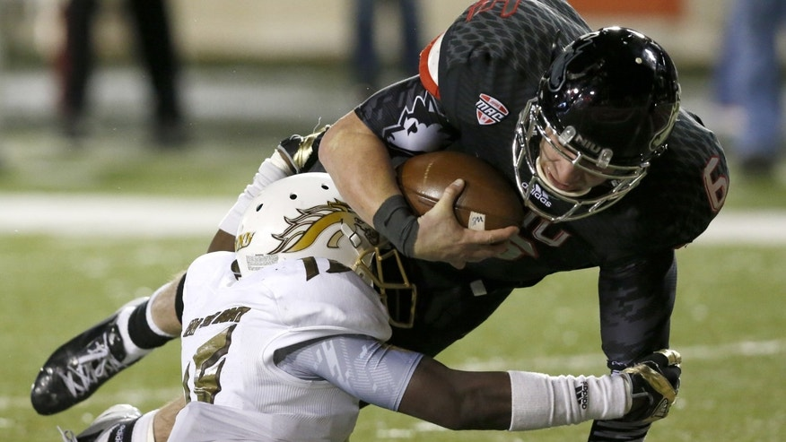 Northern Illinois quarterback Jordan Lynch (6) scores over Western Michigan defensive lineman Jamar Simpkins during the second half of an NCAA football game Tuesday, Nov. 26, 2013, in DeKalb, Ill. (AP Photo/Charles Rex Arbogast)