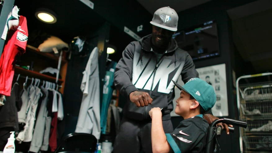 In this Oct. 18, 2013 photo, Philadelphia eagles quarterback Michael Vick give seven-year-old Justin Perales  a fist bump during a tour of the Eagles training facility in Philadelphia. Four years after his release from prison, Vick is one of the NFL's most active players involving charities. Though he's no longer the starting quarterback for the Eagles, he's unquestionably the team leader.  (AP Photo/ Joseph Kaczmarek)