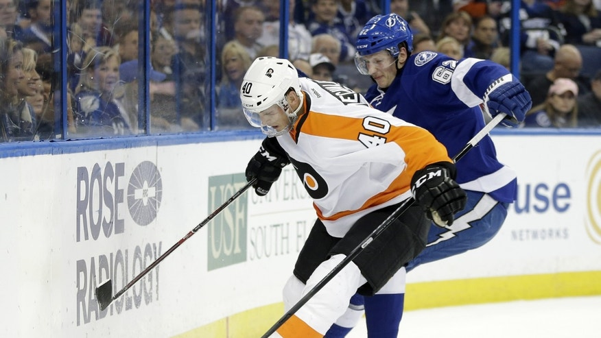 Philadelphia Flyers center Vincent Lecavalier (40) battles with Tampa Bay Lightning defenseman Andrej Sustr (62), of the Czech Reublic, for the puck behind the net during the first period of an NHL hockey game Wednesday, Nov. 27, 2013, in Tampa, Fla. (AP Photo/Chris O'Meara)