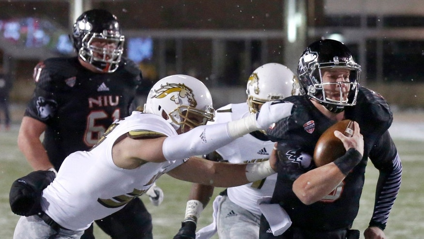 Northern Illinois quarterback Jordan Lynch carries the ball past two Western Michigan defenders during the first half of an NCAA football game Tuesday, Nov. 26, 2013, in DeKalb, Ill. (AP Photo/Charles Rex Arbogast)